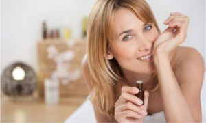 A woman holding a bottle of essential oil in her hand.